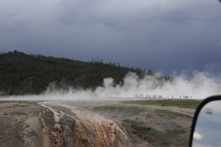 People Standing in the mist near Old Faithful